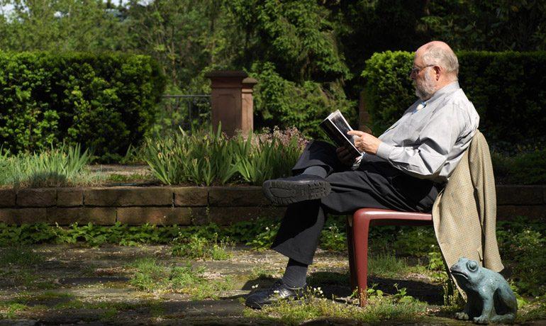 Klaus Tschira liest im Garten ein Buch