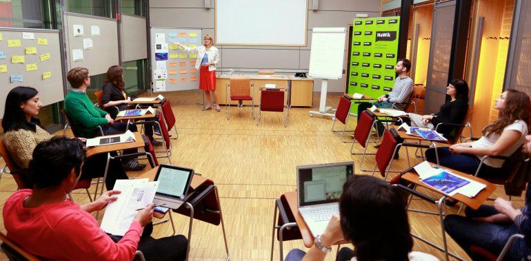 Teilnehmende des Workshops Wissenschaftskommunikation sitzen in einem Stuhlkreis, während eine Moderatorin Karteikarten an eine Pinnwand hängt.