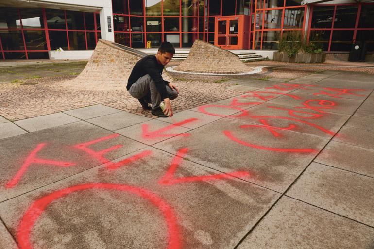 Lothar Sebastian Krapp sprüht mit Kreidespray eine symbolische Formel auf den Innenhof der Uni Konstanz